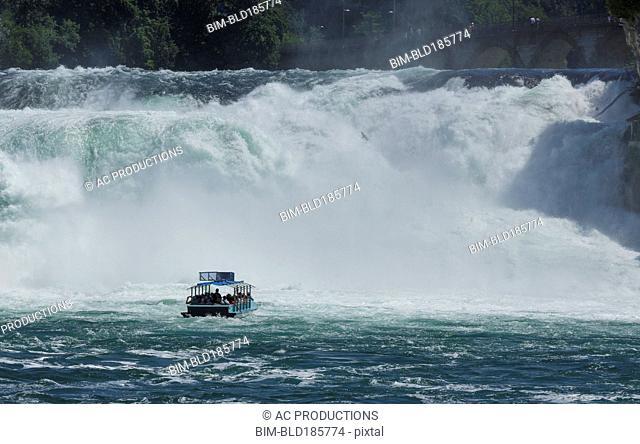 Boat floating near dramatic waterfall