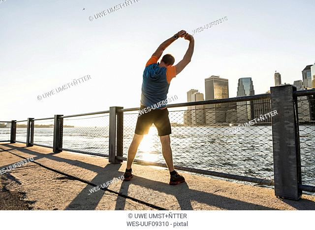 USA, Brooklyn, back view of man doing stretching exercises in the evening