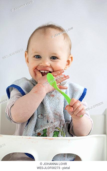 Portrait of laughing baby girl on high chair eating mush