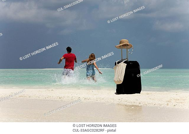 Couple abandoning luggage on beach