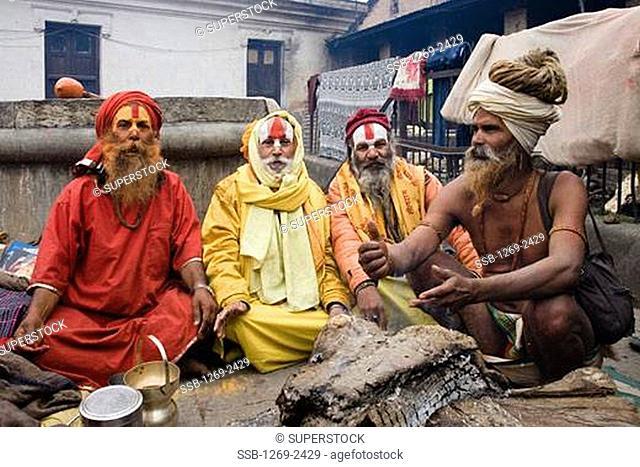 Four sadhus sitting together at a religious festival, Maha Shivaratri, Kathmandu, Nepal