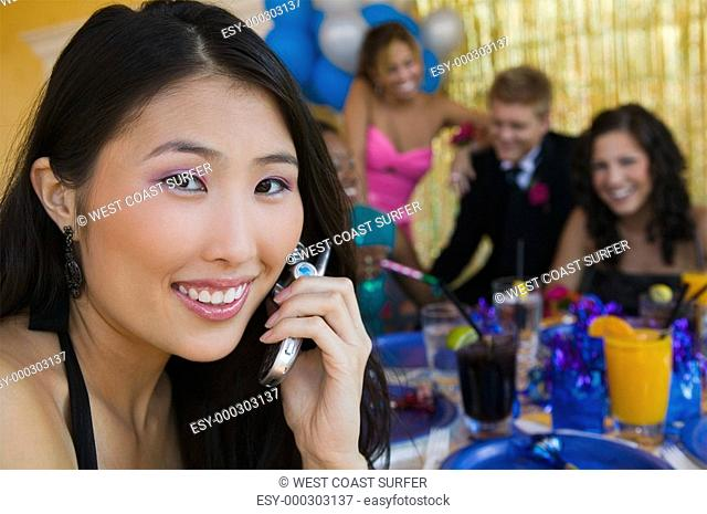 Well-dressed teenager girl using cell phone at school dance