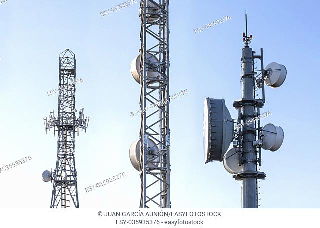Broadcast relay station antennas at rising. Telecommunications towers with blue clear sky
