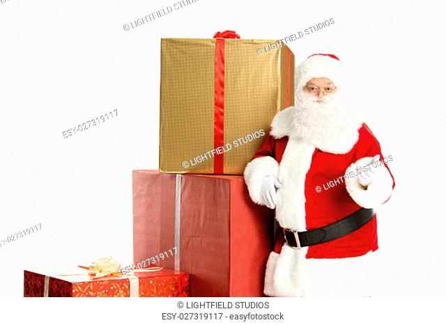 Happy Santa Claus standing with a pile of Christmas gifts isolated on white