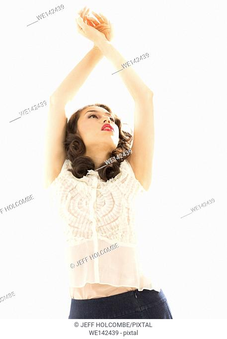 Beautiful young woman, half length in white blouse and blue denim skirt, graceful with arms over head and hands together