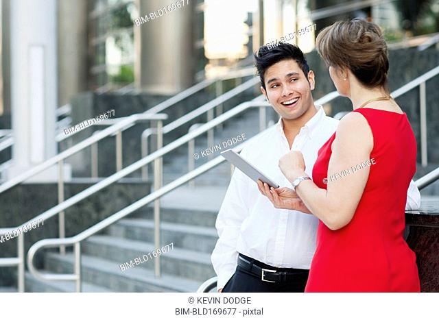 Business people using digital tablet near staircase