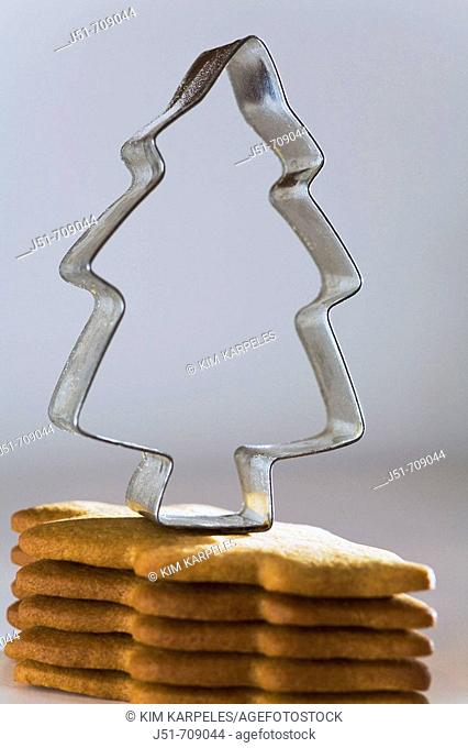 Christmas stack of homemade gingerbread cookies cut in Christmas tree shape, metal cookie cutter
