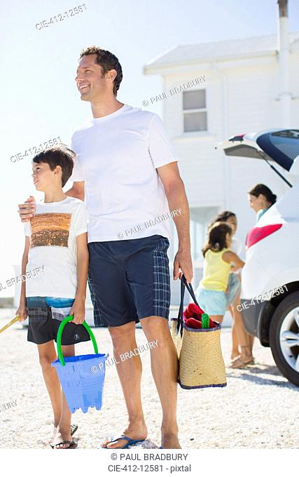 Father and son holding beach gear by car