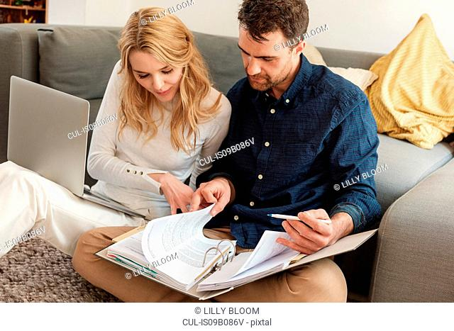 Couple with laptop looking at paperwork in ring-binder
