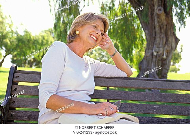 portrait, park-scene, blond woman, middle of 50, wearing bright trousers and top, sits relaxed with a book and her glasses in her hand on a bench under a tree...