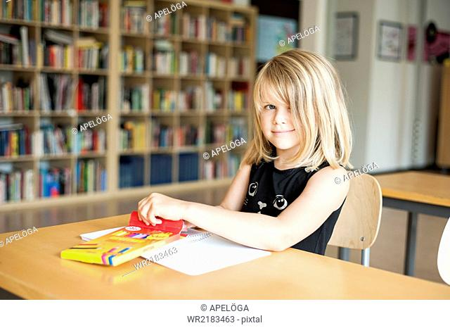 Portrait of girl coloring at desk in classroom