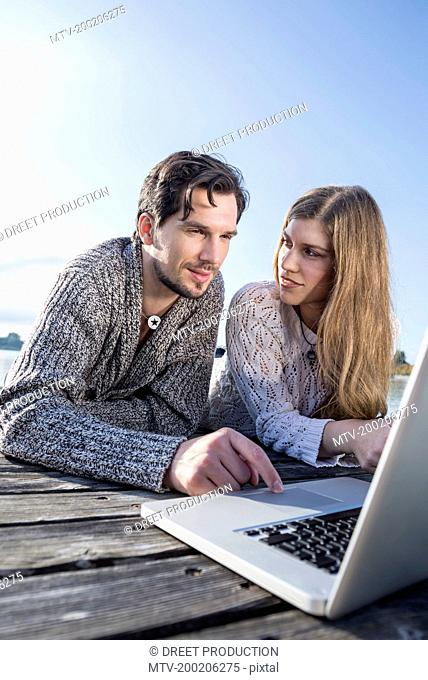 Portrait young couple laptop computer outdoors