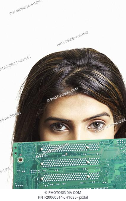 Portrait of a young woman peeking over a circuit board