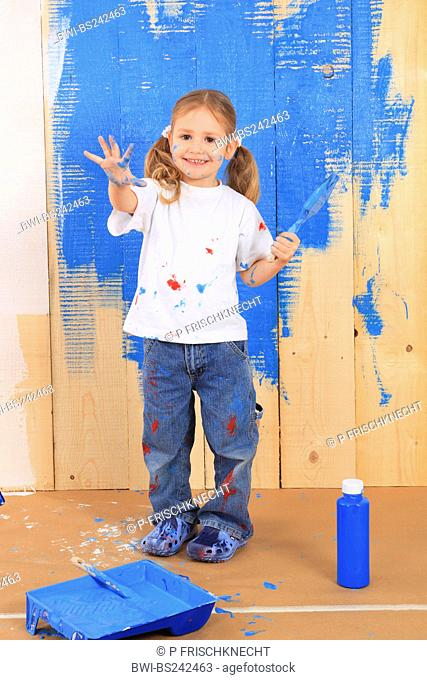 little girl painting a wooden wall blue
