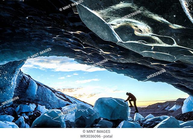 Side view of person climbing up on ice rock at the entrance to a glacial ice cave