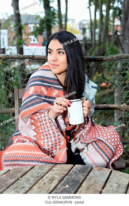 Young woman wrapped in blanket having coffee, Hampstead Heath, London