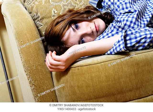 Pretty young woman lying on sofa, looking at camera