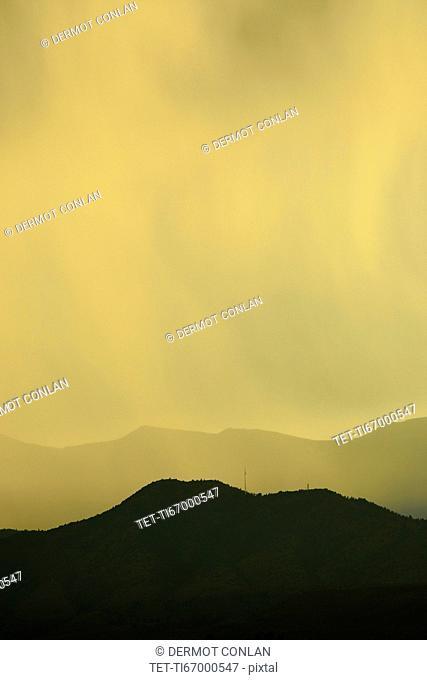 USA, Colorado, Denver, Rain against colorful sky above rocky mountains