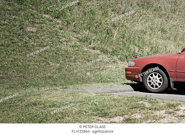 Red car in parking lot by grass