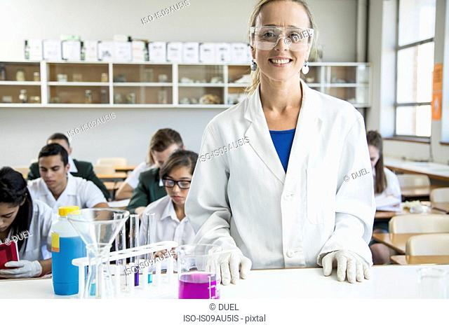 Teacher in lab, students studying in background