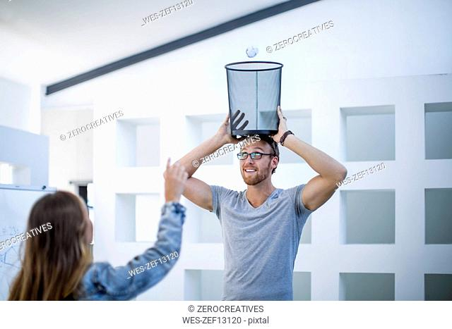 Colleagues in office throwing crumpled paper into waste paper basket