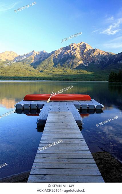 Red canoe on dock at Pyramid Lake with Pyramid mountain, Jasper National Park, Alberta, Canada