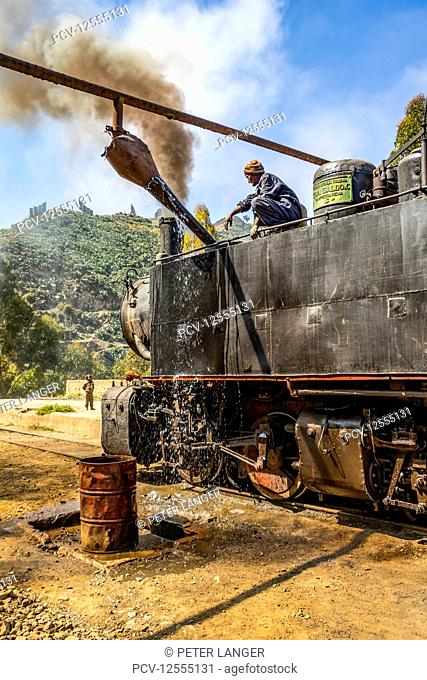 Engineer adding water to the Ansaldo 442 steam locomotive built in 1938, used for transporting cargo from the port city of Massawa to the capital Asmara;...