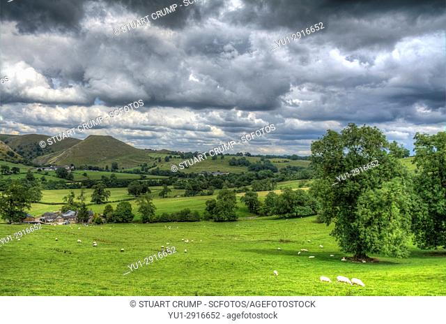 HDR image of storm clouds over sheep on a hill side in the countryside at Dovedale in Derbyshire UK