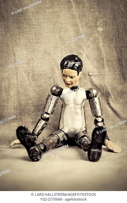 Pensive and depressed male toy doll sitting and looking down. Old fashioned retro design