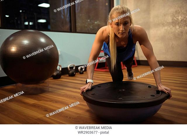 Fit woman exercising with bosu ball