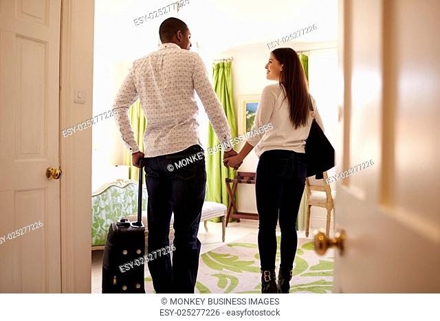 Young multi ethnic couple walk in to a hotel room, back view