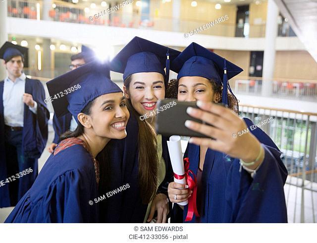 Female college graduates in cap and gown taking selfie
