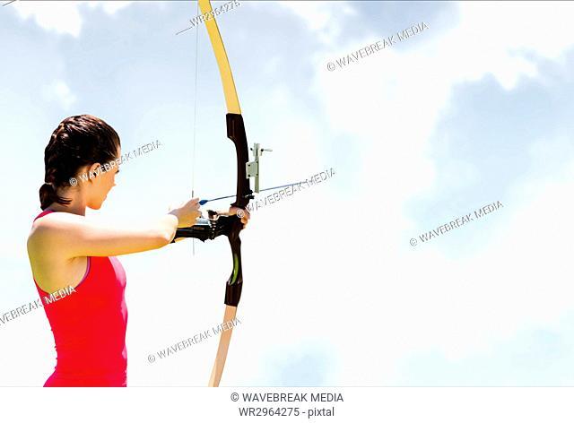 Woman archery against sky
