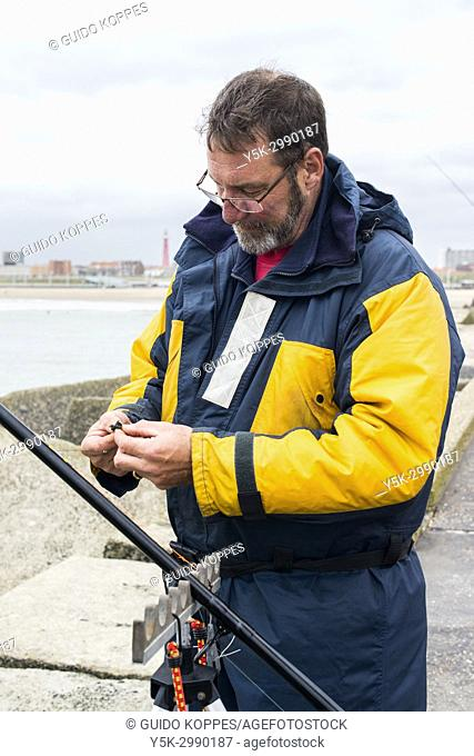 Scheveningen, Netherlands. Retired amature fisherman and his fishing rod on the harbor's north pier. After retirement many men enjoy the outdoors and go fishing...
