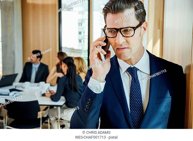 Businessman on the phone with meeting in background