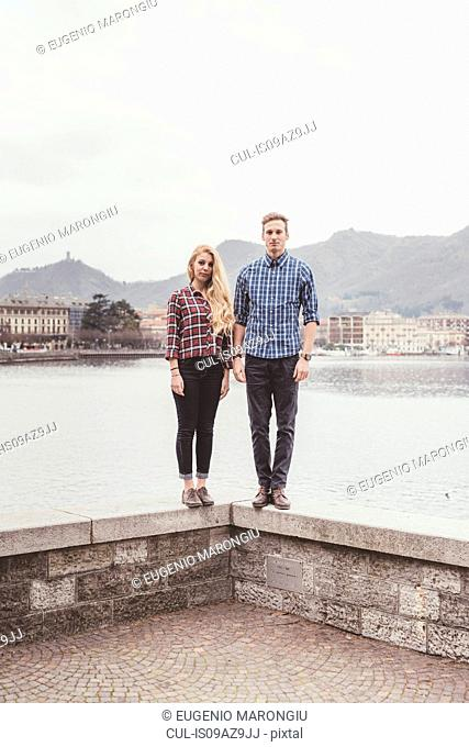 Portrait of young couple standing on harbour wall, Lake Como, Italy