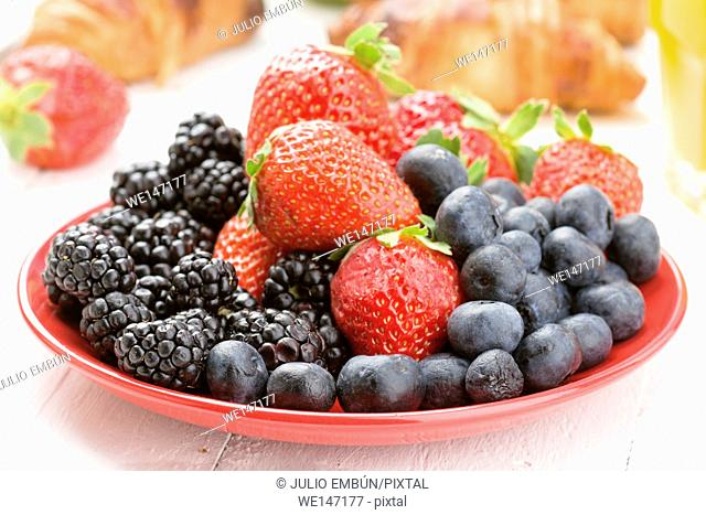 breakfast plate full of ripe berries and croissants on white wood