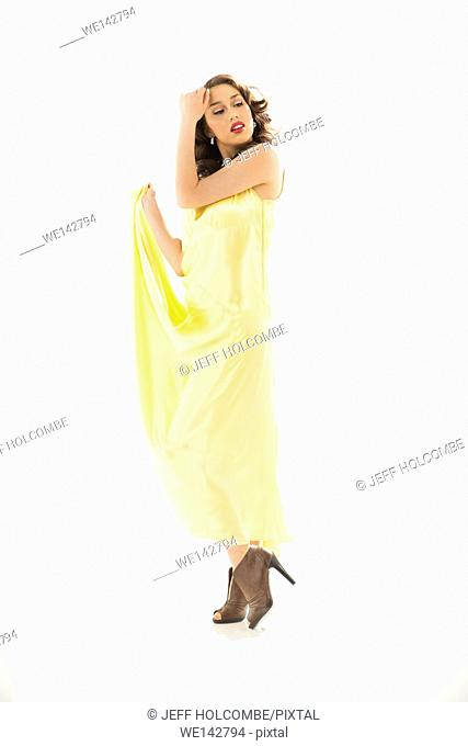 Beautiful young woman in vintage yellow dress, full length in brown heels, one arm raised to forehead