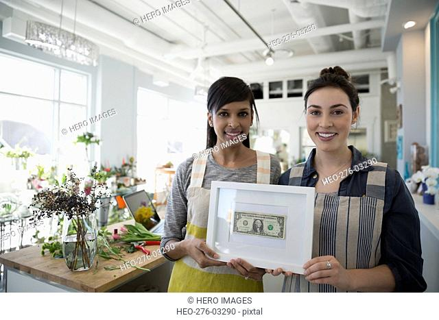 Portrait confident florists holding framed first earned dollar