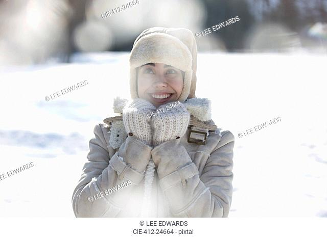 Woman in warm clothing smiling in snow