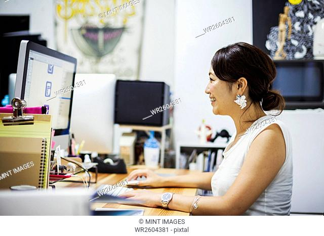 Design Studio. A woman sitting at a desk using a computer