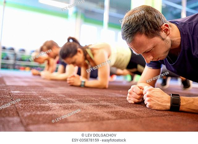 fitness, sport, exercising and people concept - man with heart-rate tracker at group training doing plank exercise in gym