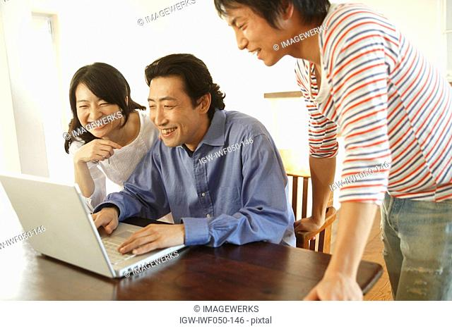 Young man with mother and father using laptop