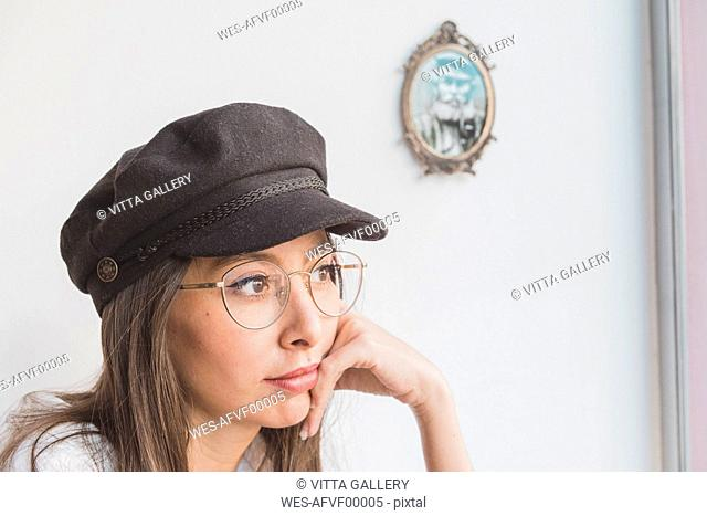 Stylish young woman wearing glasses and cap thinking