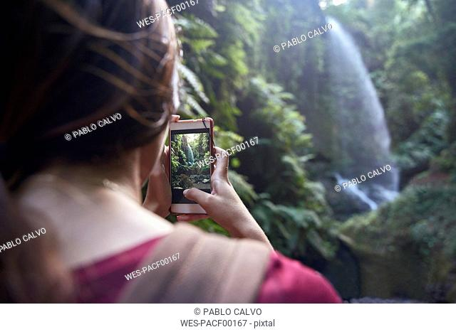 Spain, Canary Islands, La Palma, woman taking a cell phone picture of a waterfall in a forest