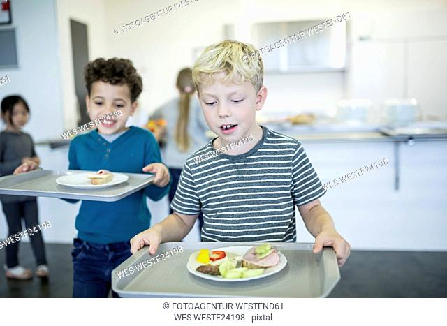 Pupils carrying trays in school canteen