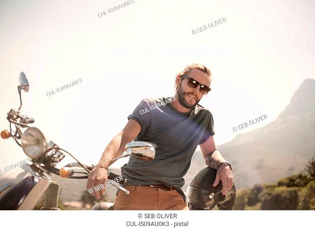 Portrait of mid adult man standing beside moped