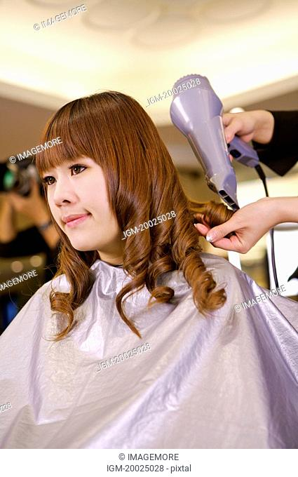 Young woman having her hair curled and dried, Hair Salon