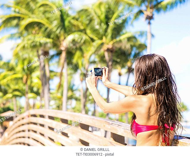 Young woman photographing wooden bridge