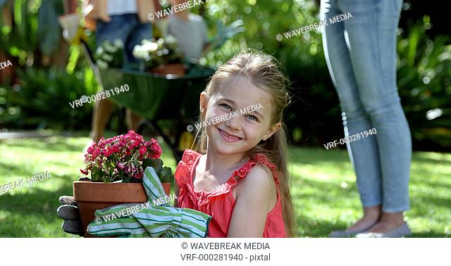 Portrait of cute girl is holding a flowerpot in front her family gardening